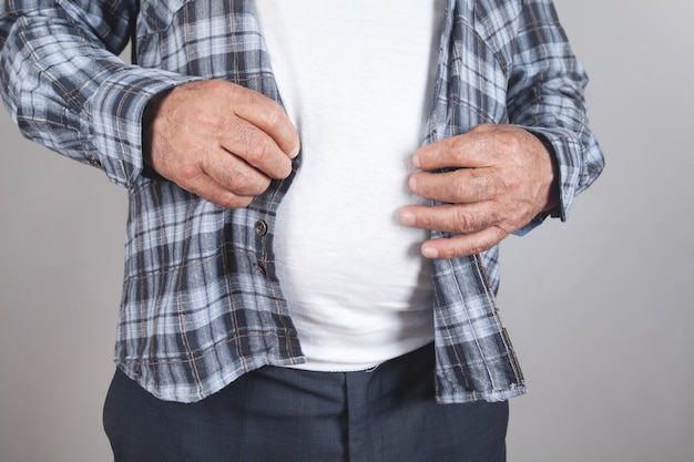 灰色の背景のシャツのボタンを締める太った男ダイエット