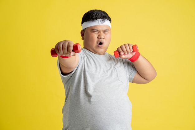 Fat man is exercising by lifting weights