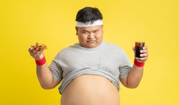 Толстяк счастлив есть пиццу и пить колу