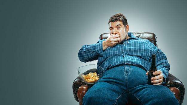 Толстяк сидит в коричневом кресле, эмоционально смотрит телевизор