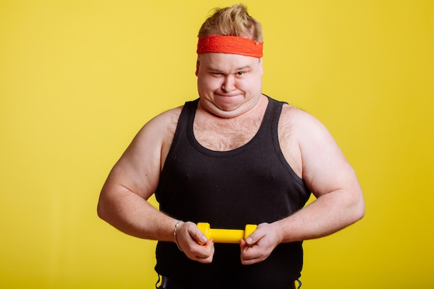 Fat man try to lift small yellow dumbell