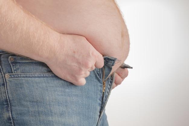 Fat man trying to put on pants. big paunch
