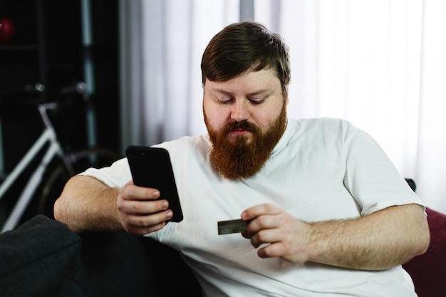 Fat man types the number of a credit card in his phone sitting on the couch