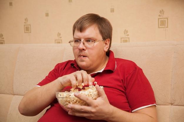 Толстяк смотрит телевизор, ест попкорн