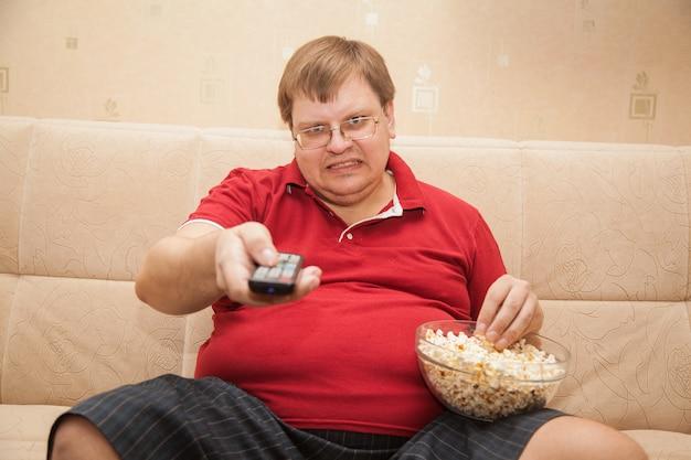 ポップコーンを食べてテレビを見ているデブ男