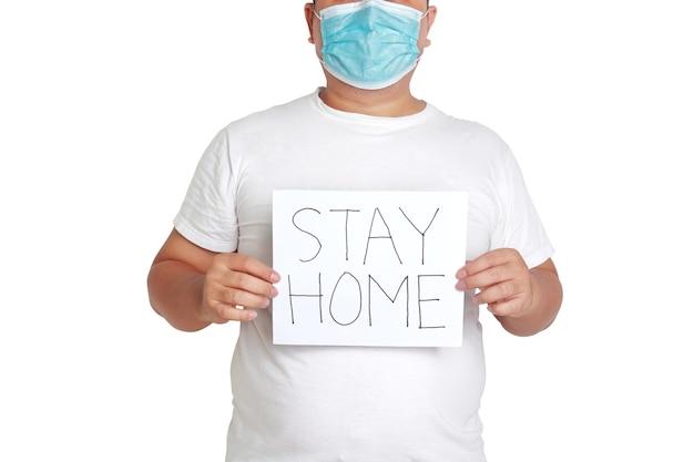 マスクと白い服を着た太った男紙の看板を持って、家にいるという言葉を書いてください。肥満者の健康問題の概念コロナウイルス感染の予防。白色の背景。孤立