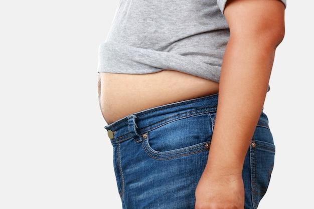 体重の多い灰色のシャツを着た太った男シャツを脱いで大きなお腹を見せてください。健康上の問題があるさまざまな病気のリスクがあります。減量の概念。クリッピングパス