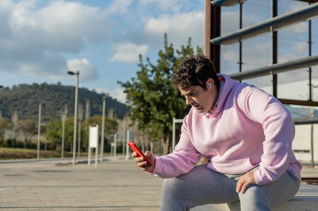 太った男はピンクのスウェットシャツとスウェットパンツ、雲と青い空を着ています