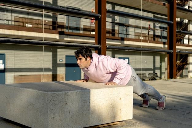 太った男はピンクのスウェットシャツを着て、スウェットパンツは街でスポーツをします