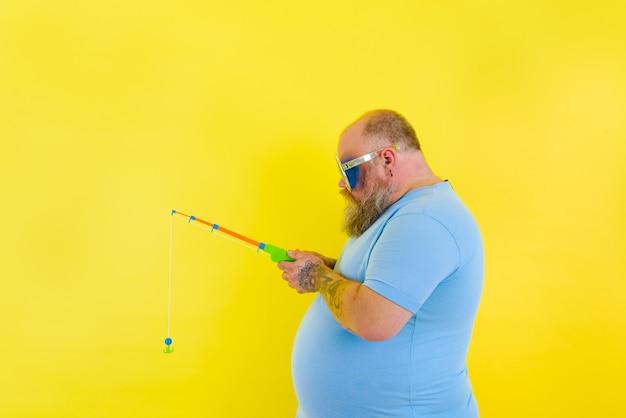 수염과 선글라스를 쓴 뚱뚱한 남자는 낚싯대에 불만이 있다