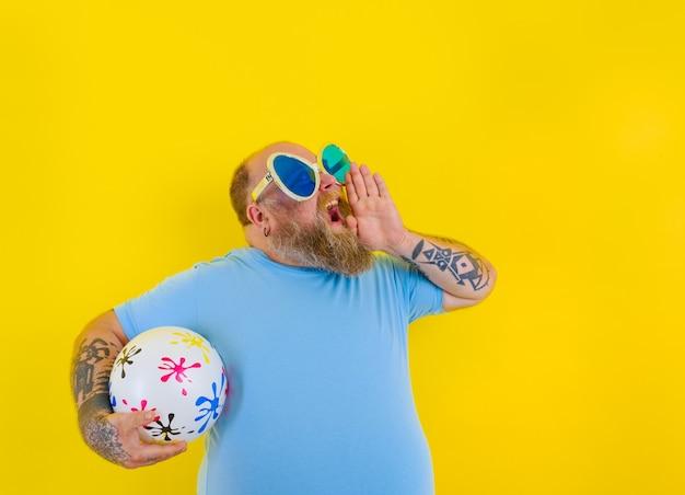 수염과 선글라스를 가진 뚱뚱한 남자가 공을 손에 들고 비명을 지른다