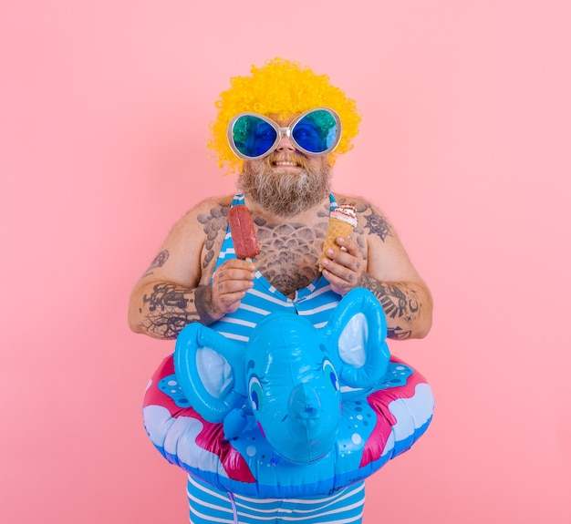あごひげとかつらを持つ太った男はアイスキャンデーとアイスクリームを食べる