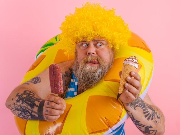 수염과 가발을 가진 뚱뚱한 남자는 아이스 캔디와 아이스크림을 먹는다