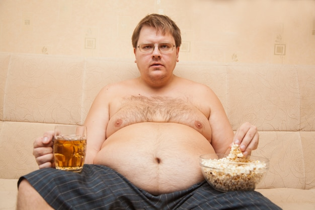 Fat man with beer belly in front of tv eats popcorn and drinks beer