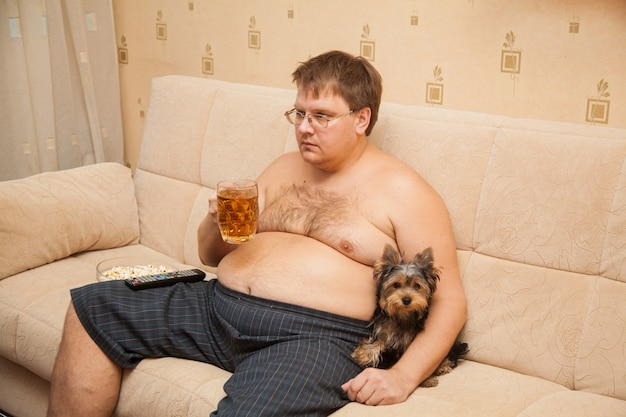 Fat man with beer belly in front of tv eats popcorn with his pet