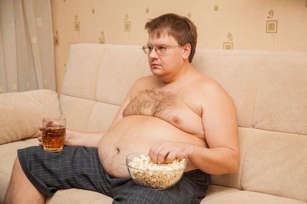 テレビの前でビール腹のデブ男がポップコーンを食べてビールを飲む