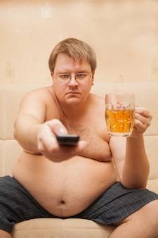 Толстяк с пивным животом перед телевизором ест попкорн и пьет пиво