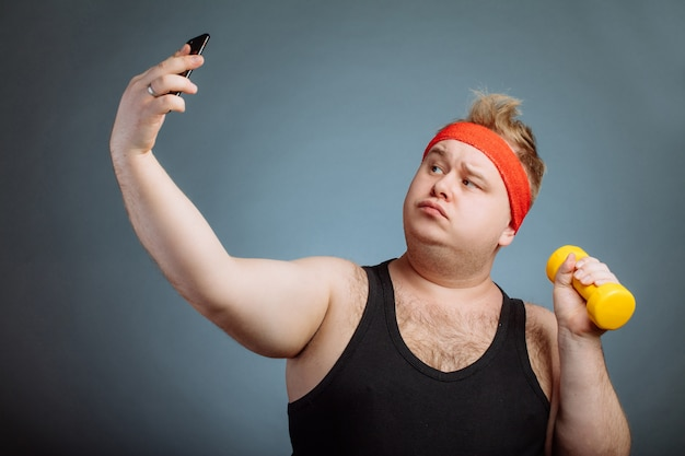 Fat man with big belly, holding dumbbell, doing selfie on grey wall