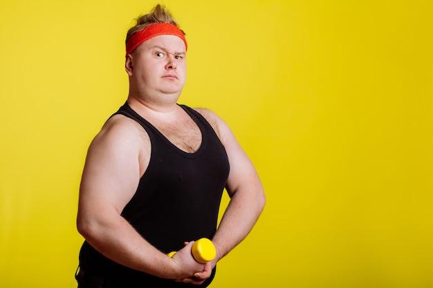 黄色の壁にダンベルのデブ男。太っている人への動機