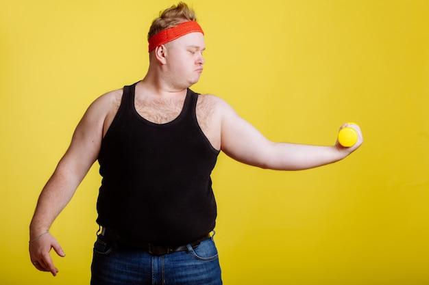 Толстяк с гантелями на желтой стене. мотивация для полных людей