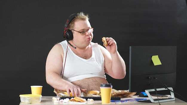 Fat man with glasses and headphones sitting at a table eating and playing a pc game at home. self-isolation, quarantine