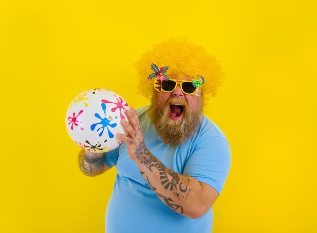 머리에 가발을 쓰고 선글라스를 쓴 뚱뚱한 남자는 공을 가지고 즐겁게 놀고 있다