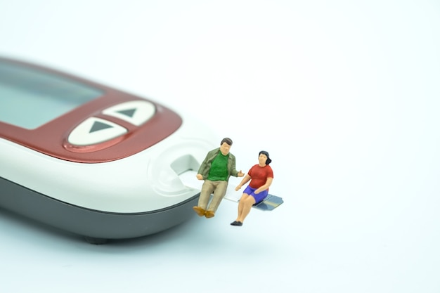 Fat man and woman miniature people figure sitting on test strip with glucose meter