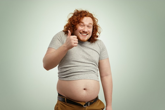 Fat overweight redhead caucasian man in undersized t-shirt showing thumps up and smiling