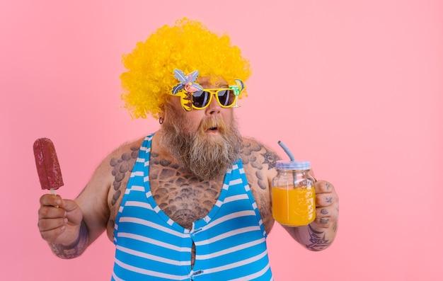 수염과 가발을 가진 뚱뚱한 생각에 잠겨있는 남자는 아이스 캔디를 먹고 주스 과일을 마신다