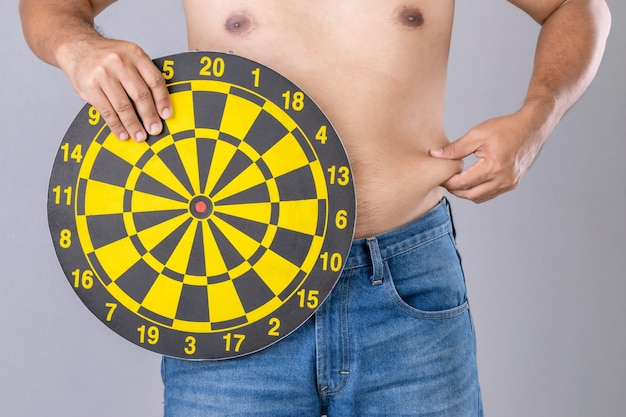 Fat people holding round yellow dartboard beside his belly position. target of losing weight concept.