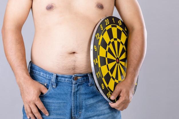 Толстые люди держат круглую желтую доску для дротика у его живота. цель концепции похудения.