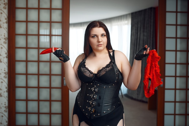 Fat perverse woman in erotic lingerie holds red pepper and panties.