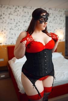 黒と赤のエロティックなランジェリーの太った変態女性。
