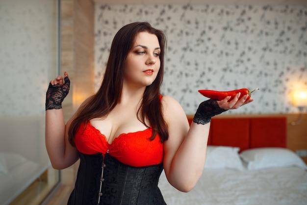 エロティックなランジェリーの太った変態女性は赤唐辛子を保持しています。