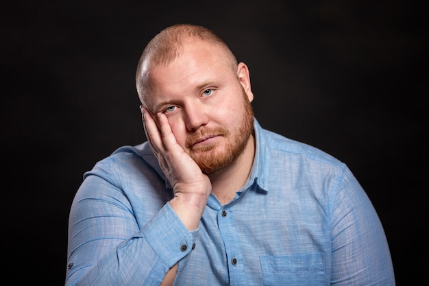 Fat red-haired man with a beard and mustache in a blue shirt is sad, propping his head in his hands.