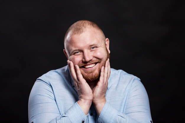Fat redhead man in a blue shirt smiles cute. he pressed his palms to his face. black background.