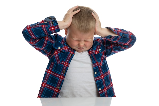 A fat sad boy sits at the table and holds his head with his hands. schoolboy in a plaid shirt. back to school. isolated. close-up.