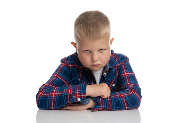 A fat sad boy sits at the table. schoolboy in a plaid shirt. back to school. isolated. close-up.