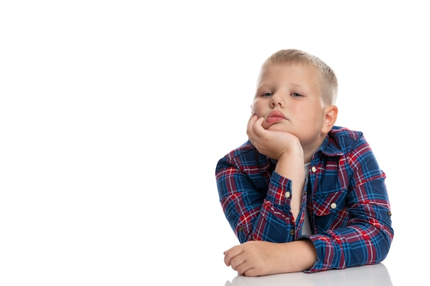A fat, sad boy sits at a table with his head in his hands. schoolboy in a plaid shirt. back to school. isolated. close-up.