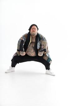 큰 배를 가진 뚱뚱한 세련된 수염 난 백인 남자가 민족 기모노를 입고 포즈를 취하고 춤을 추고 있습니다