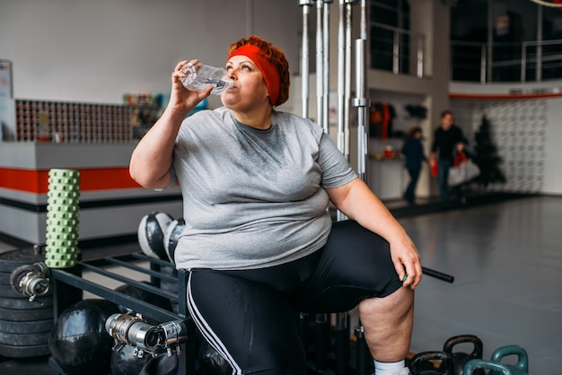 Fat sweaty woman drinks water after active training in gym. calories burning, obese female person on workout in sport club