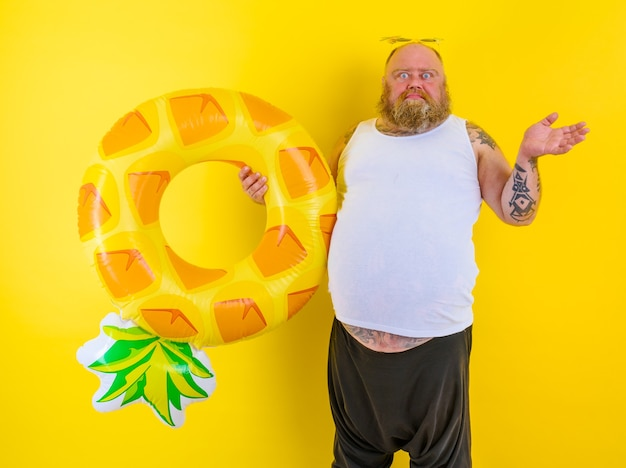 Fat thoughtful man with wig in head is ready to swim with a donut lifesaver