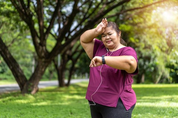 スマートウォッチから時間や心拍数をチェックする太った女性アジア人。減量のアイデアの概念のために屋外で運動する