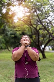 減量のアイデアの概念のための屋外で太った女性のアジアの運動。