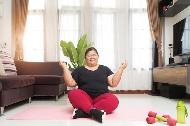 Толстая женщина азиатская работая жизнеспособность релаксации на положении лотоса дома, концепции идеи спорта и воссоздания.