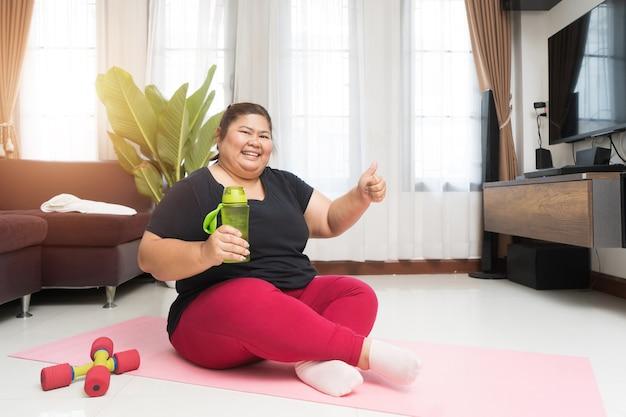 Толстая азиатка женщины держа бутылку с водой при показывая большие пальцы руки вверх работая дома, концепции идеи спорта и воссоздания.