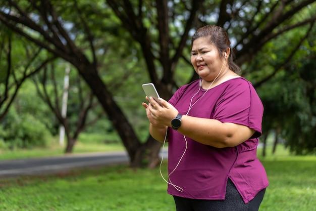 音楽を聴きながらスマートフォンを持っている太った女性アジア人。減量のアイデアの概念のために屋外で運動する