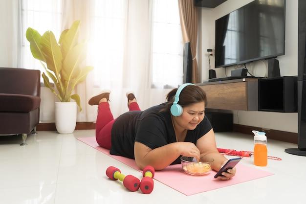 Жизнеспособность релаксации толстой женщины азиатская используя умный телефон и нездоровую пищу дома, концепцию идеи спорта и воссоздания.