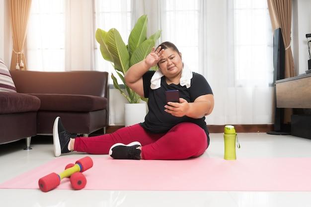 Толстая азиатка женщины берет перерыв работая с использованием умного телефона дома, концепции идеи спорта и отдыха.
