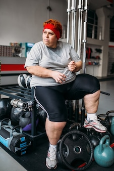 Fat woman drinks water after training in gym